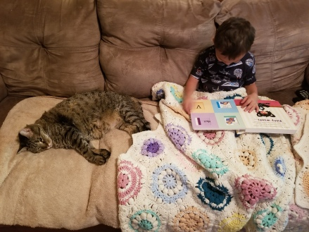 Lil' Man is sharing his favorite Bad Kitty book with Rocky. Rocky is of course taking a cat nap.
